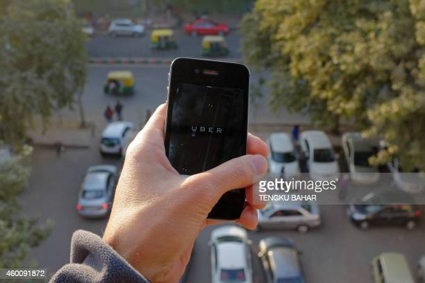The Uber smartphone app used to book taxis using its service is pictured over a parking lot as autorickshaws ply a road in the Indian capital New...