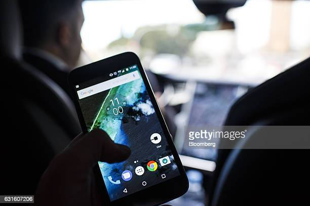 The Uber Technologies Inc ridehailing service app sits on a smartphone screen in the rear of an Uber Technologies Tesla Motors Inc Model S electric...