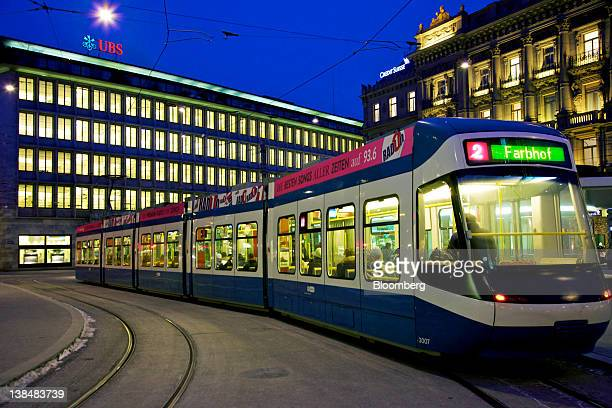 The UBS AG headquarters left are seen next to the Credit Suisse AG headquarters right as a tram passes the buildings in Zurich Switzerland on Tuesday...