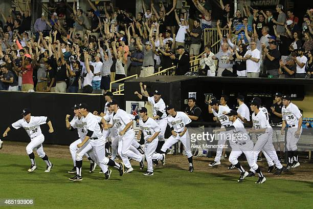 The UCF Knights baseball team celebrates in the ninth inning after defeating the Florida Gators 43 during an NCAA baseball game at Jay Bergman Field...