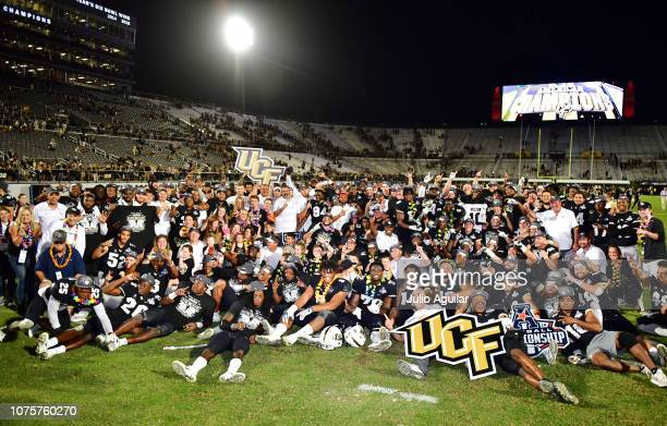 The UCF Knights celebrate with the American Athletic Conference trophy after defeating the Memphis Tigers 5641 in the American Athletic Championship...