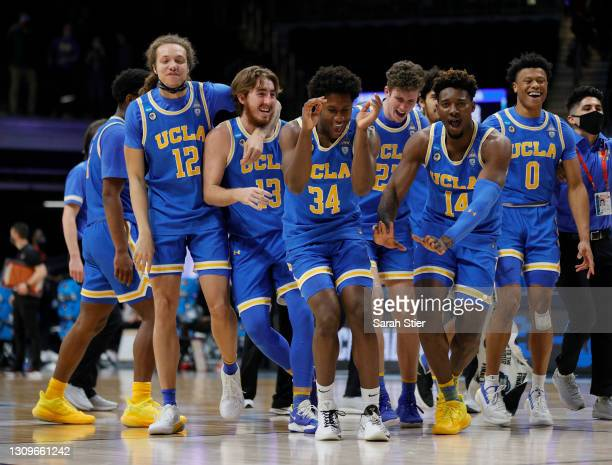 The UCLA Bruins celebrate after defeating the Alabama Crimson Tide in the Sweet Sixteen round game of the 2021 NCAA Men's Basketball Tournament at...