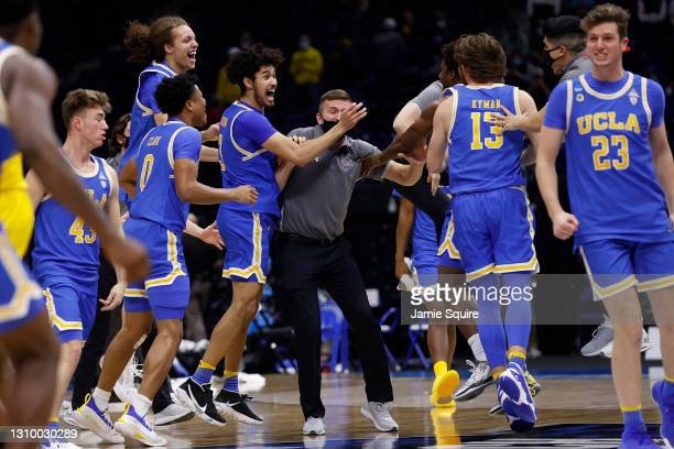 The UCLA Bruins celebrate defeating the Michigan Wolverines 51-49 in the Elite Eight round game of the 2021 NCAA Men's Basketball Tournament at Lucas...