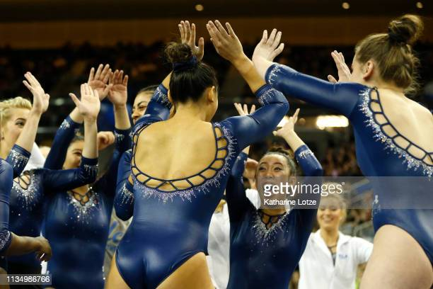 The UCLA Bruins celebrate Kyla Ross' perfect 10 on beam during a meet against Stanford at Pauley Pavilion on March 10 2019 in Los Angeles California