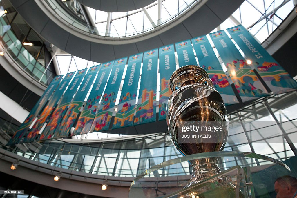 The UEFA European Championship football trophy is displayed in front of individual host city banners at a launch event for the 2020 euros logo in London on September 21, 2016. The 2020 UEFA European Championship will see matches hosted in 13 cities across Europe, with the semi-finals and final staged at Wembley Stadium in London in July 2020. / AFP / JUSTIN