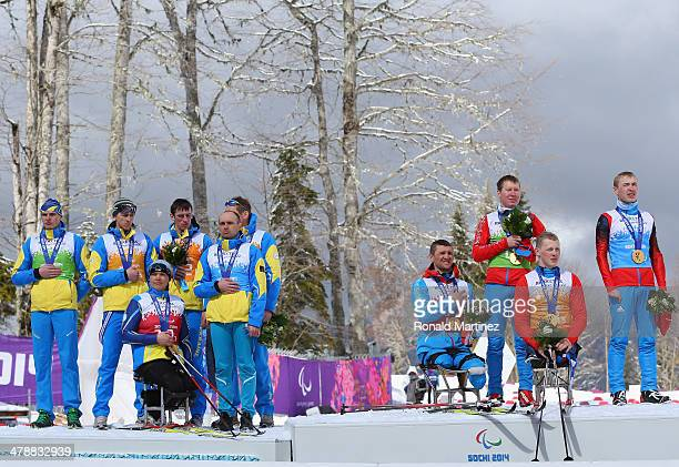 The Ukraine team cover their silver medals as the Russian team stand for the national anthem of Russia during the medal ceremony for the Mixed 4 x...