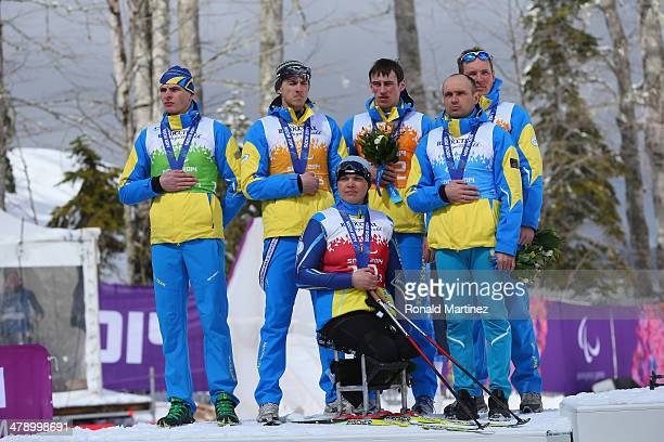 The Ukraine team covers their silver medals for the Mixed 4 x 25km Relay CrossCountry Skiing event medals ceremony during day eight of Sochi 2014...