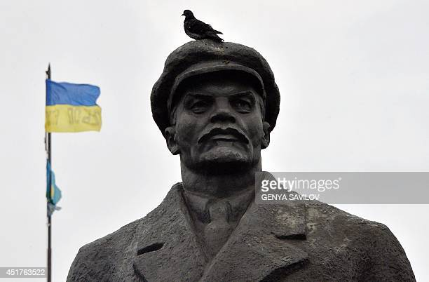 The Ukrainian flag flies on top of the city hall of the eastern Ukrainian city of Slavyansk in the background of a Lenin's monument on July 6 2014...