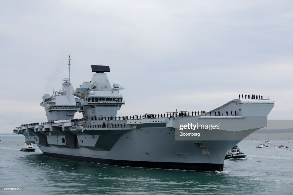 The U.K.'s Royal Navy new aircraft carrier, HMS Queen Elizabeth arrives at its home port in Portsmouth, U.K., on Wednesday, Aug. 16, 2017. The largely French-designed ship will carry 40 aircraft and about 700 crew members was built by a joint venture between BAE Systems Plc, Babcock International Group Plc and Thales SA. Photographer: Luke MacGregor/Bloomberg via Getty Images
