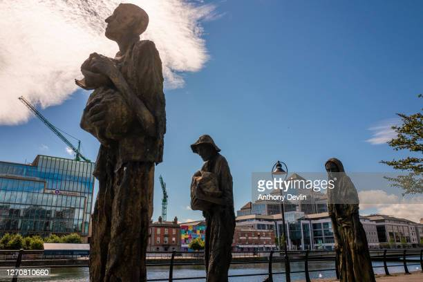 The Ulster Bank Capital Markets buildings are seen behind statues outside EPIC, The Irish Emigration Museum in the Docklands area on August 04, 2020...