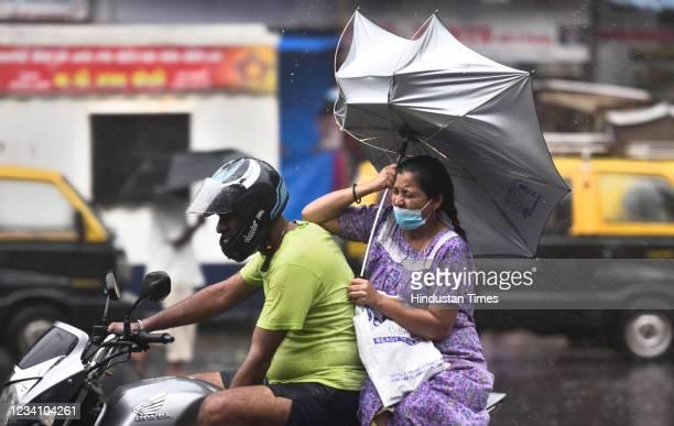 The umbrella of a woman riding pillion turns upside amid heavy rain and gusty wind at Chinchpokli, on July 21, 2021 in Mumbai, India. )