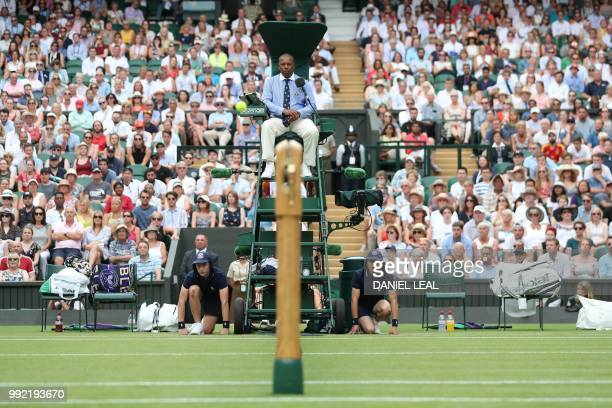 The umpire and ballboys watch as the ball flies over the net as Spain's Rafael Nadal returns to Kazakhstan's Mikhail Kukushkin in their men's singles...