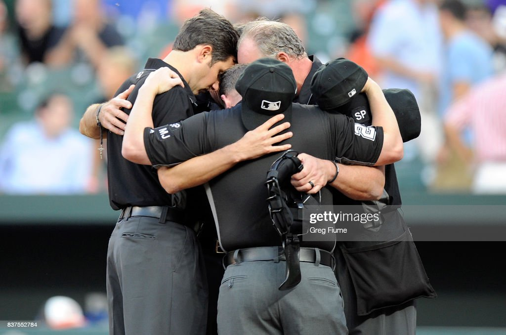 The umpire crew huddles up before the game between the Baltimore Orioles and the Oakland Athletics at Oriole Park at Camden Yards on August 22, 2017 in Baltimore, Maryland.