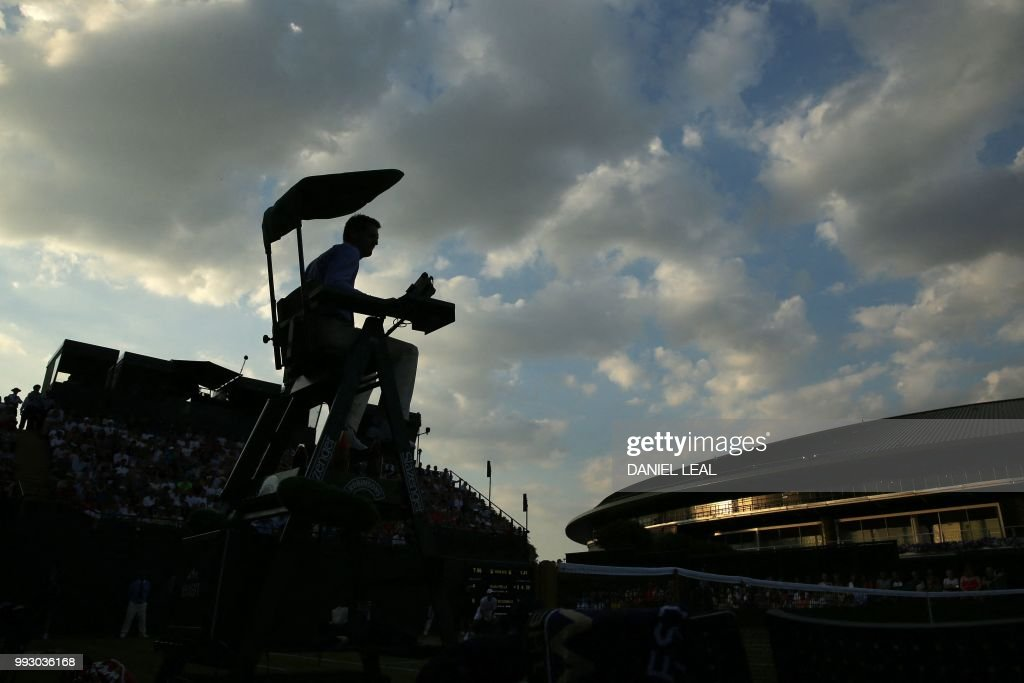 TOPSHOT - The umpire is silhouetted as Argentina's Guido Pella plays US player Mackenzie McDonald during their men's singles third round match on the fifth day of the 2018 Wimbledon Championships at The All England Lawn Tennis Club in Wimbledon, southwest London, on July 6, 2018. - McDonald won the match 6-4, 6-4, 7-6. (Photo by Daniel LEAL-OLIVAS / AFP) / RESTRICTED
