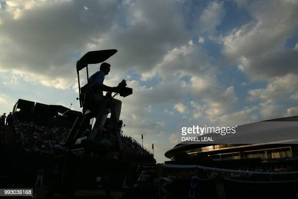 TOPSHOT The umpire is silhouetted as Argentina's Guido Pella plays US player Mackenzie McDonald during their men's singles third round match on the...