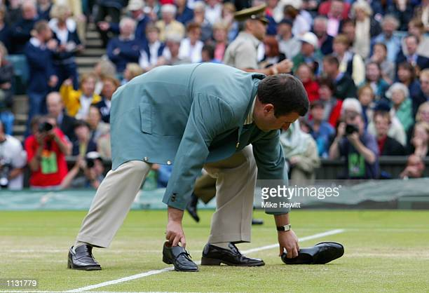 The umpire picks a male streaker's shoes off the court during the Mens Singles Final at the All England Tennis Championships at the All England Lawn...
