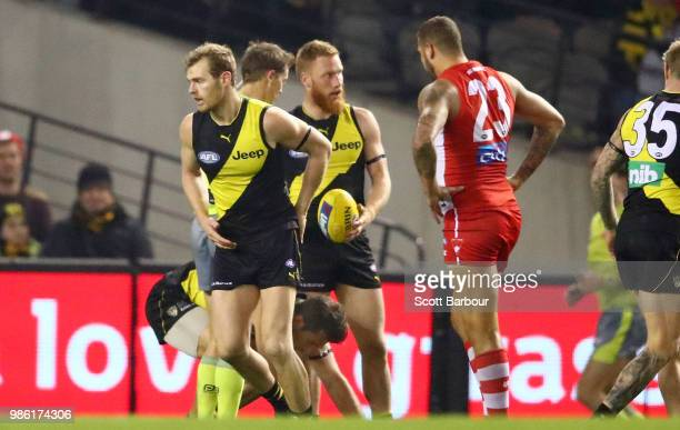 The umpire speaks to Lance Franklin of the Swans after he hit Alex Rance of the Tigers in the throat during the round 15 AFL match between the...