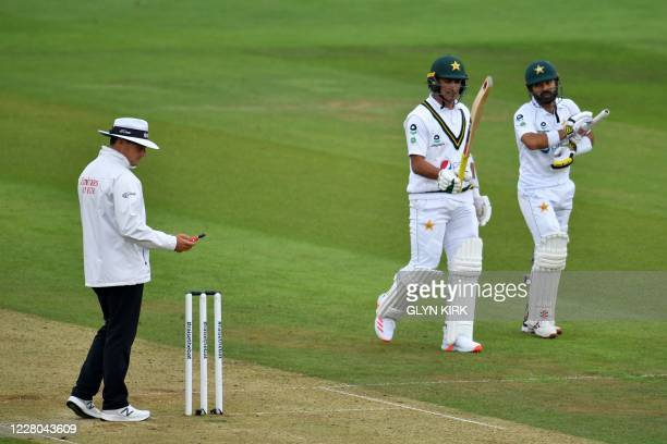 The umpire takes a light-reading as the batsmen walk back to the dressing room as play is delayed for bad light on the second day of the second Test...