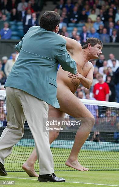 The umpire tries to stop a male streaker running onto Centre Court as Lleyton Hewitt of Australia plays David Nalbandian of Argentina during the Mens...