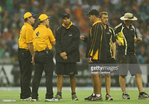 The umpires have a discussion with the groundsmen as rain delays play during the Big Bash League semifinal match between the Perth Scorchers and the...