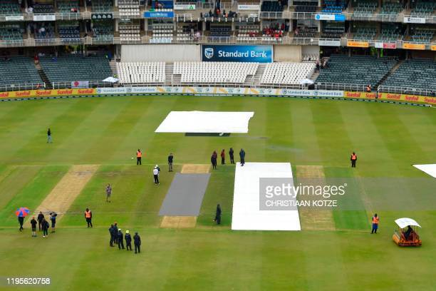 The umpires inspect the pitch before the first day of the fourth Test cricket match between South Africa and England at the Wanderers Stadium in...