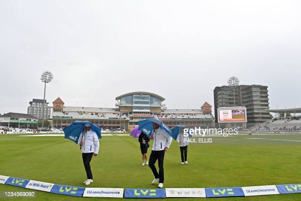 The umpires shelter under umbrellas after carrying out an inspection as play is delayed by rain on the fifth day of the first Test match between...