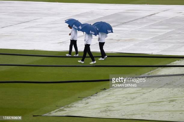 The umpires shelter under umbrellas as they inspect the pitch after rain disrupted play on the third day of the first Test cricket match between...