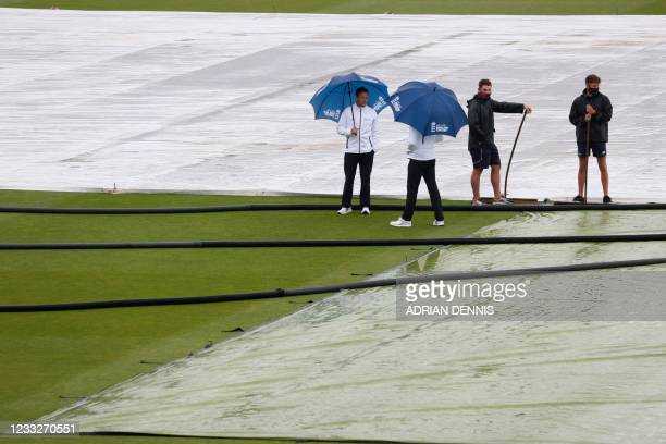 The umpires shelter under umbrellas as they inspect the pitch as groundstaff stand by after rain disrupted play on the third day of the first Test...