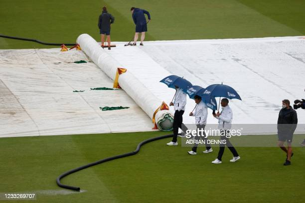 The umpires shelter under umbrellas to inspect the pitch as groundstaff work after rain disrupted play on the third day of the first Test cricket...