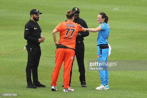 The umpires speak to Sophie Devine of the Scorchers and Megan Schutt of the Strikers as the match is abandoned due to rain during the Women's Big...