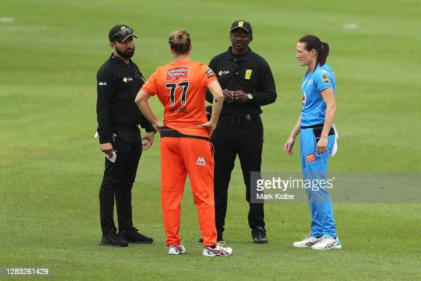 The umpires speaks to Sophie Devine of the Scorchers and Megan Schutt of the Strikers as the match is abandoned due to rain during the Women's Big...