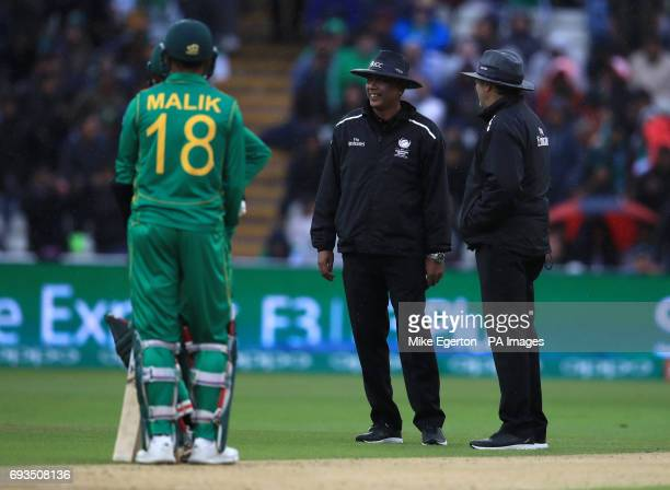 The umpires take the Pakistan and South African players off the pitch as the rain starts to fall during the ICC Champions Trophy Group B match at...