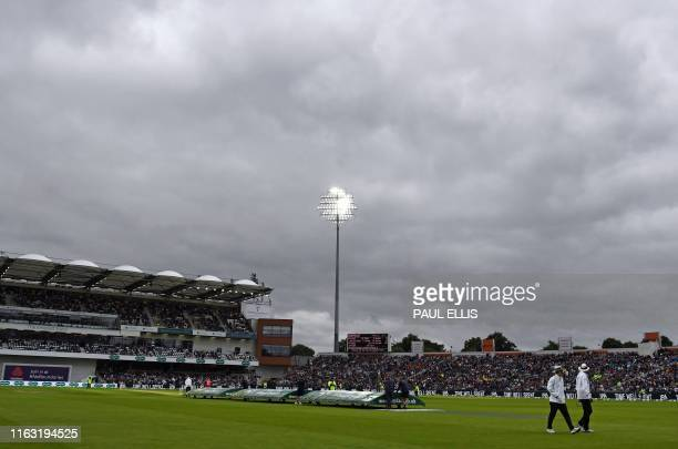 The umpires walk off the pitch after bad light stops play during the first day of the third Ashes cricket Test match between England and Australia at...