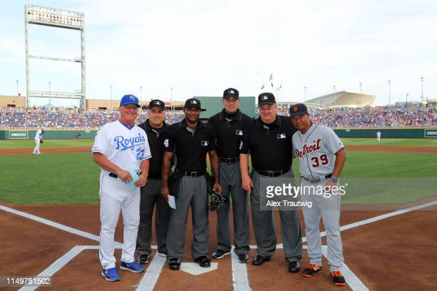 The umpiring crew poses for a photo at home plate with Mike Jirschele of the Kansas City Royals and Ramon Santiago of the Detroit Tigers prior to the...