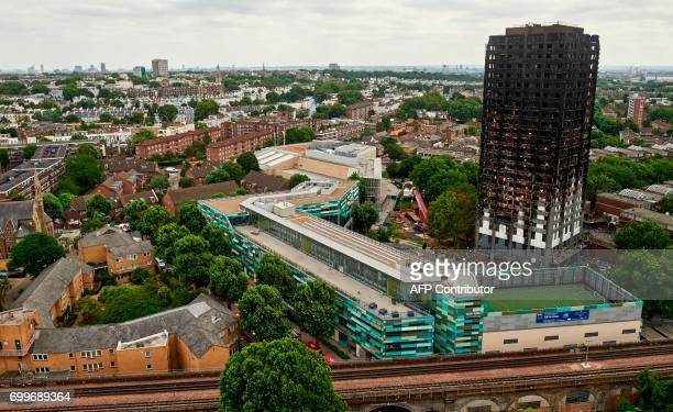 The unburned lower floors with untouched cladding still in place are pictured with the burnt out upper floors above at the remains of the Grenfell...