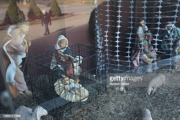 The unconventional nativity scene at St Susanna Parish in Dedham MA which includes baby Jesus inside a black metal cage is pictured on Dec 5 2018...