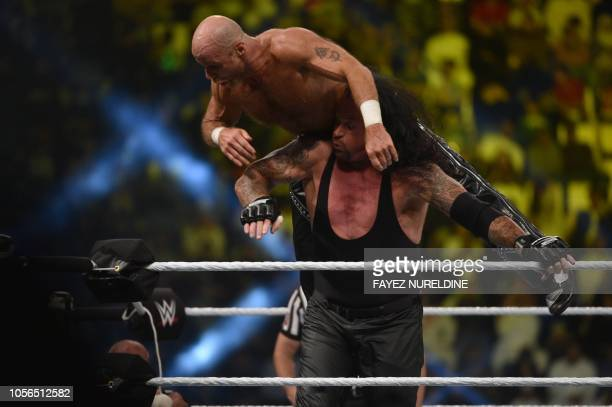The Undertaker vies with Shawn Michaels during a tag team match as part of as part of the World Wrestling Entertainment Crown Jewel payperview at the...