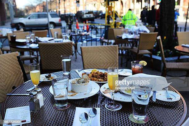 The unfinished meals of fleeing customers are left on tables at an outdoor restaurant near the scene of a twin bombing at the Boston Marathon on...