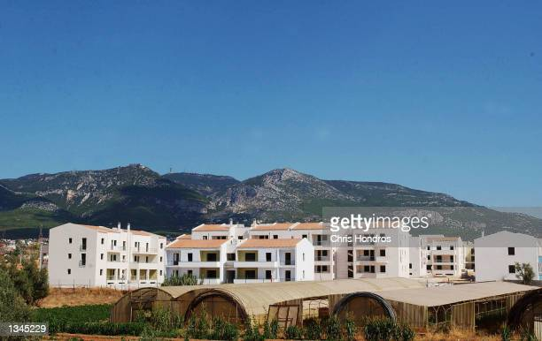 The unfinished Olympic Village lies next to mountains August 14, 2002 in a suburb of Athens, Greece. The area will eventually house thousands of...