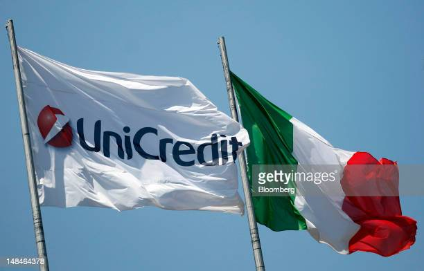 The UniCredit SpA logo sits on a flag as it flies alongside the national flag of Italy outside the company's headquarters in Rome, Italy, on Tuesday,...