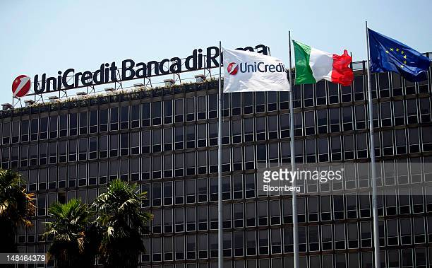 The UniCredit SpA logo sits on a flag, left, as it flies alongside the national flag of Italy, center, and the Eropean Union flag outside the...