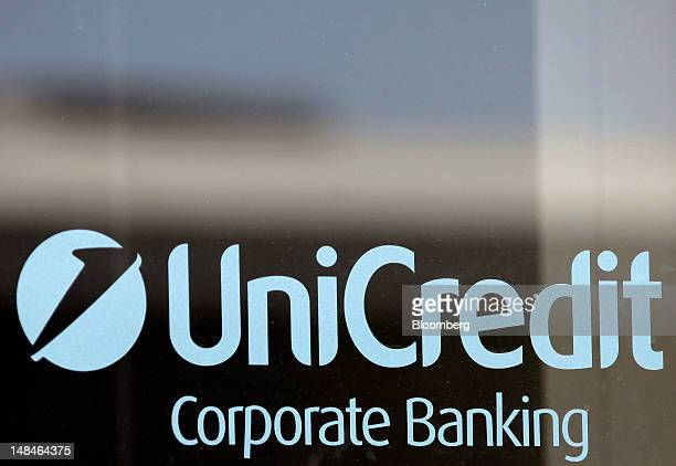 The UniCredit SpA's logo is sits on a window at one of the company's bank branches in Rome, Italy, on Tuesday, July 17, 2012. UniCredit SpA and...
