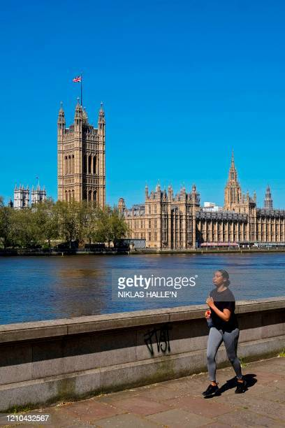 The Union flag flutters in the breeze on top of the Victoria Tower part of the Palace of Westminster as a woman exercises beside the River Thames in...