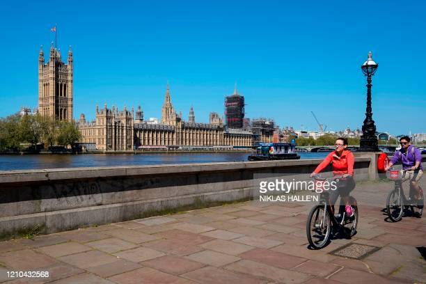 The Union flag flutters in the breeze on top of the Victoria Tower part of the Palace of Westminster as people cycle beside the River Thames in...