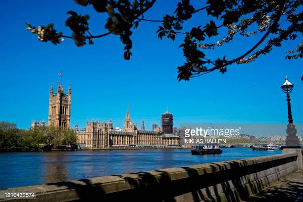 The Union flag flutters in the breeze on top of the Victoria Tower part of the Palace of Westminster seen from the south bank of the River Thames in...