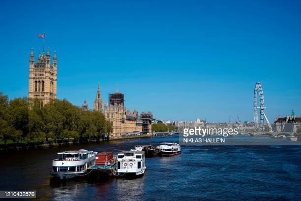 The Union flag flutters in the breeze on top of the Victoria Tower part of the Palace of Westminster as boats are seen moored on the River Thames in...