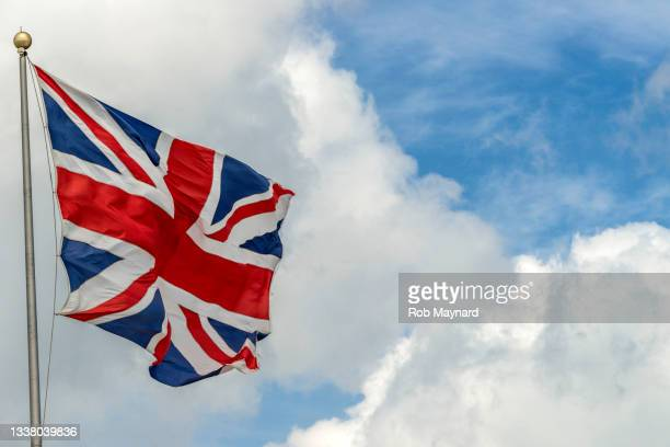 the union jack and clouds - conservative party uk stock pictures, royalty-free photos & images