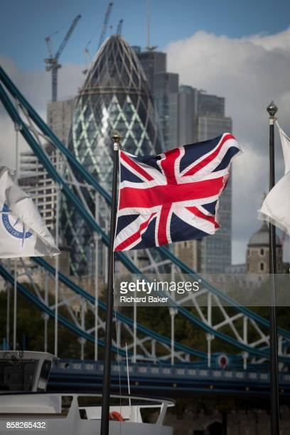 The Union Jack flag flies in the foreground of Tower Bridge and construction work in progress next to the Swiss Re Building in the capital's...