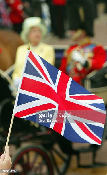 The Union Jack flag is waved in the air as Britain's Queen Elizabeth II and her husband the Duke of Edinburgh arrive at Buckingham Palace after...