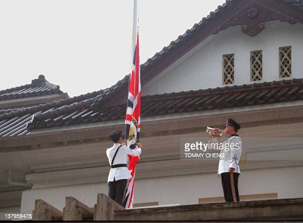 The Union Jack is lowered to the sound of a lone buglar playing the Last Post at Government House the Patten's official residence 30 June with little...